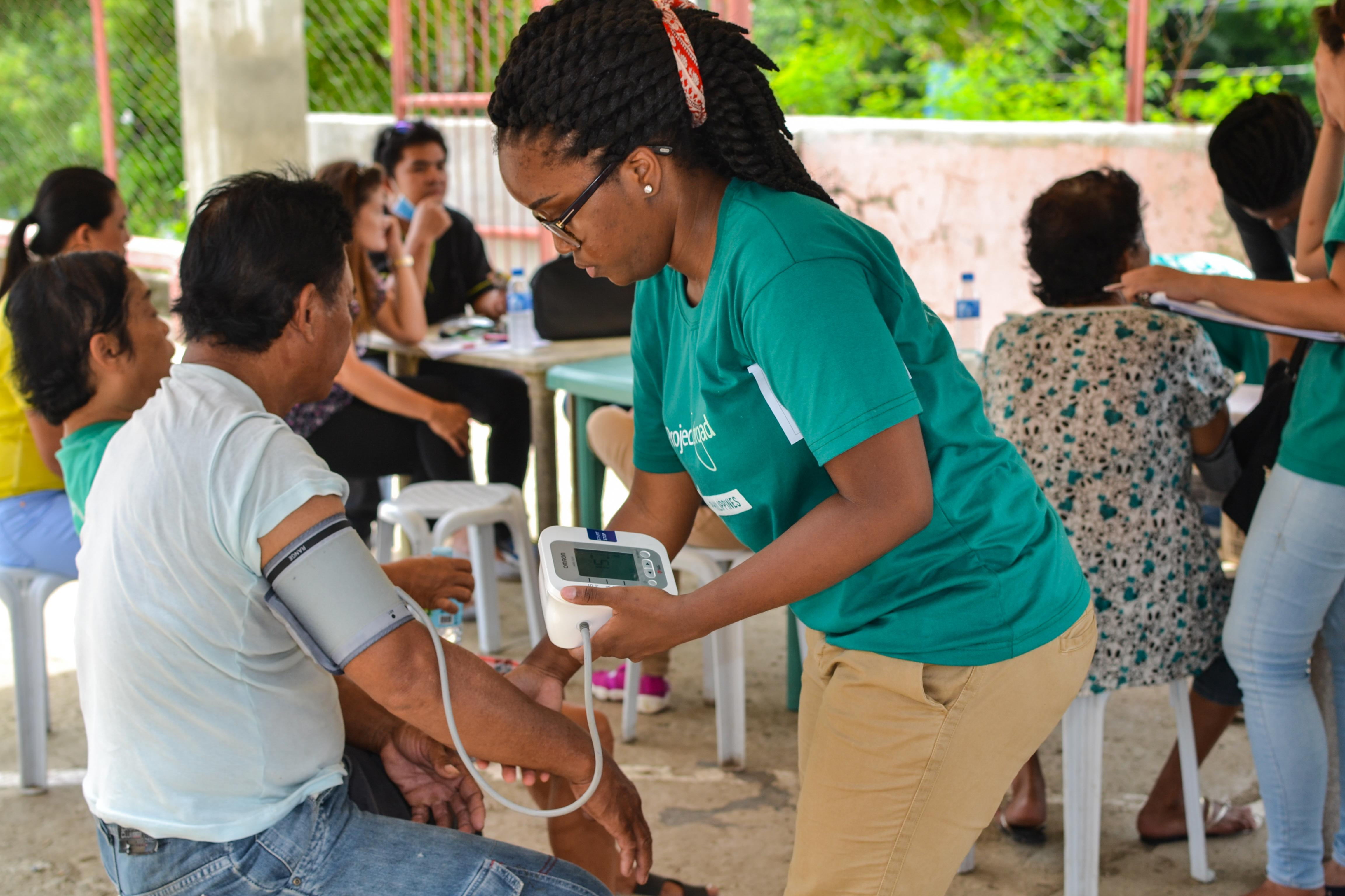 During an outreach, a student takes the blood pressure of a patient during her Public Health internship in the Philippines.